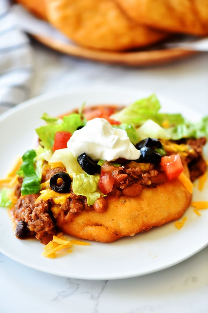 Easy Navajo Tacos are Indian fry breads topped with chili, cheese and all your favorite taco fixings. Life-in-the-Lofthouse.com