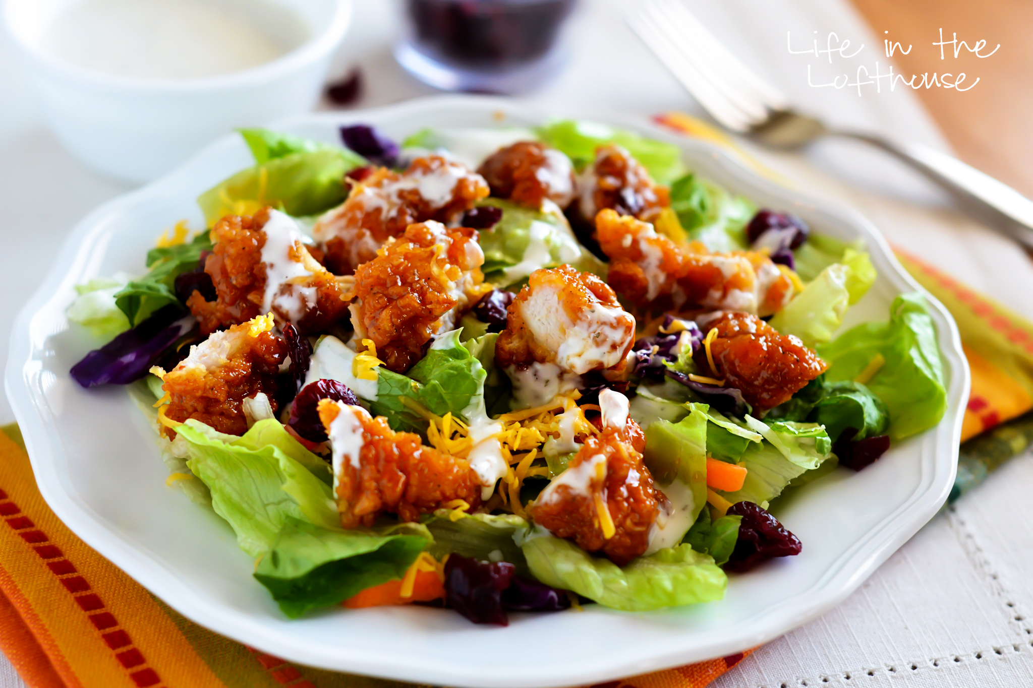 This delicious salad is full of crunchy romaine lettuce, dried cranberries, shredded carrots, cheese, and of course those amazing sticky chicken fingers. Life-in-the-Lofthouse.com