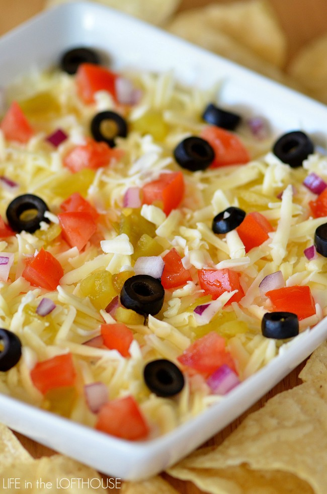 This dip has a thick and creamy layer of sour cream that's been flavored with ranch seasoning, and topped with shredded Monterey Jack cheese, diced green chilies, tomatoes and olives. Life-in-the-Lofthouse.com