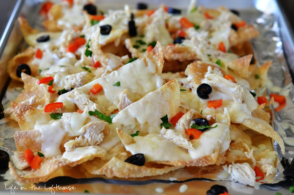 These Italian nachos are made with crispy wontons, grilled chicken, bell peppers, and olives smothered in Alfredo sauce and cheese. Life-in-the-Lofthouse.com