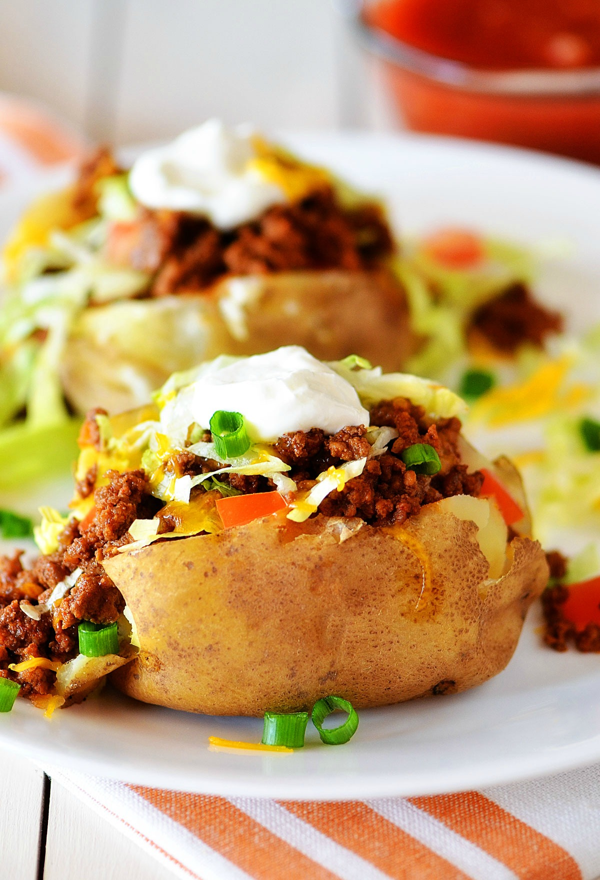 Taco Potatoes are loaded with seasoned ground beef, cheese, lettuce, sour cream and salsa all over a baked potato. Life-in-the-Lofthouse.com
