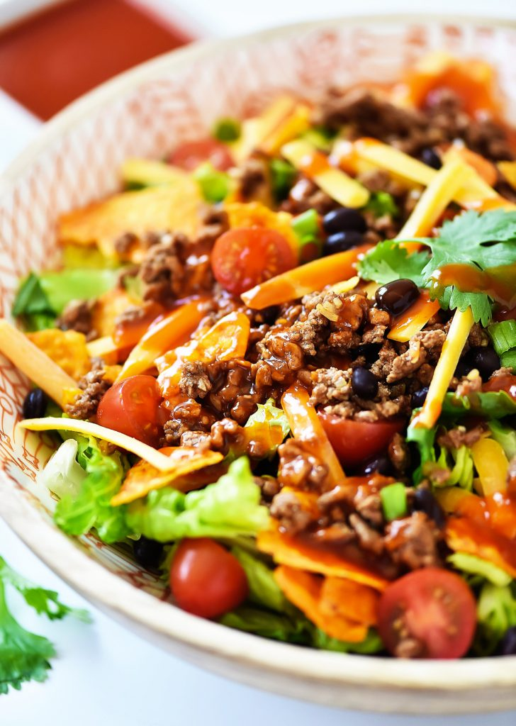 This Doritos Taco Salad is loaded with seasoned ground beef, black beans and of course, Nacho Cheese Doritos. Life-in-the-Lofthouse.com