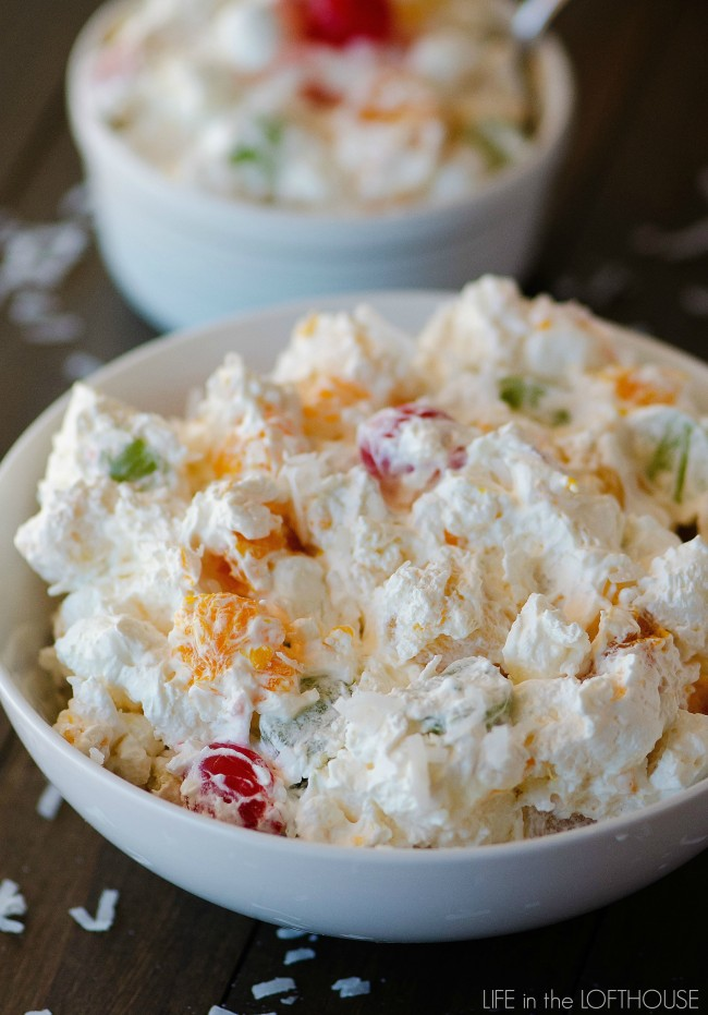 Ambrosia salad has apples, oranges, pineapples and grapes all tossed together in whipped topping and shredded coconut. Life-in-the-Lofthouse.com