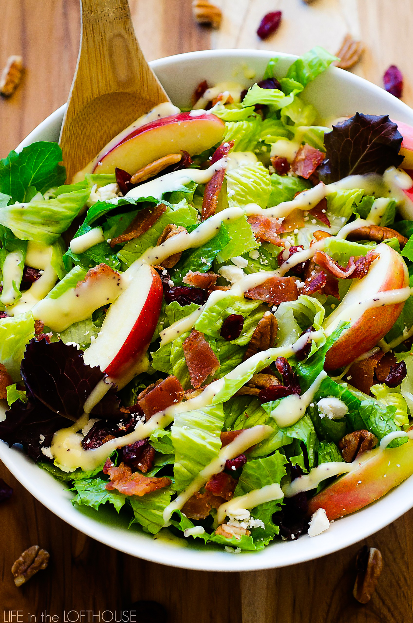 Autumn chopped salad is filled with chopped leafy greens, apples, cranberries, bacon, pecans and feta cheese. Life-in-the-Lofthouse.com