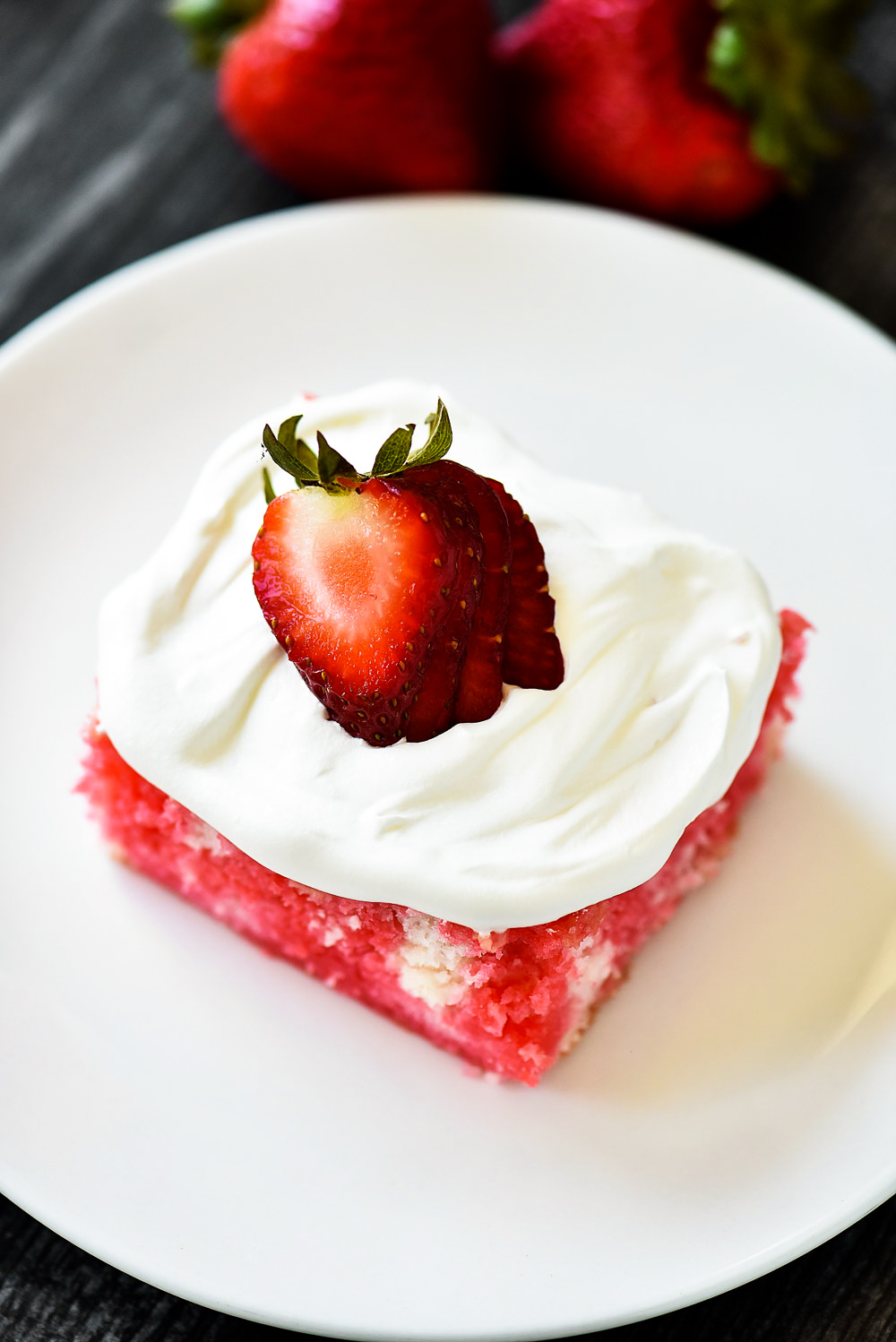 Incredibly light and delicious Strawberry Jello Poke Cake! This white cake is filled with strawberry jello and topped with fresh whipped cream and strawberries.