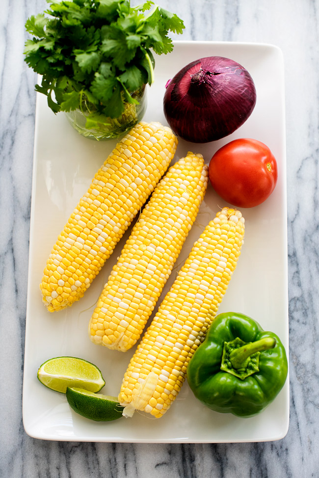 Summer corn salad is a flavorful salad filled with corn, bell peppers, tomato, red onion and fresh cilantro. Life-in-the-Lofthouse.com