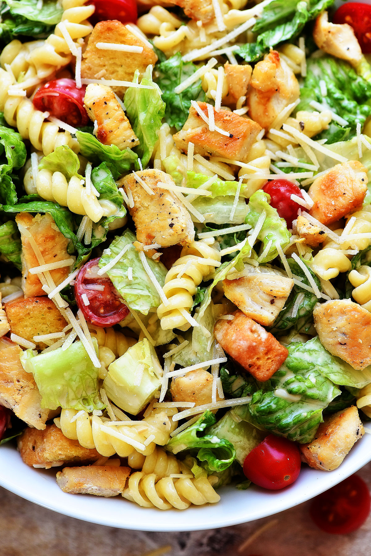 Chicken Caesar Pasta Salad is filled with grilled chicken, rotini pasta, croutons and tomatoes over a bed of romaine lettuce. Life-in-the-Lofthouse.com