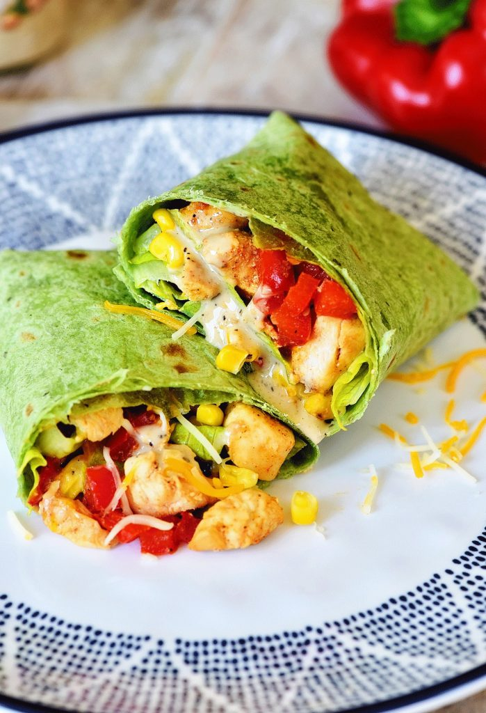 Southwest Chicken Caesar Wraps have tender seasoned chicken, black beans, corn, bell pepper and a few other goodies all wrapped up in a spinach tortilla. Life-in-the-Lofthouse.com