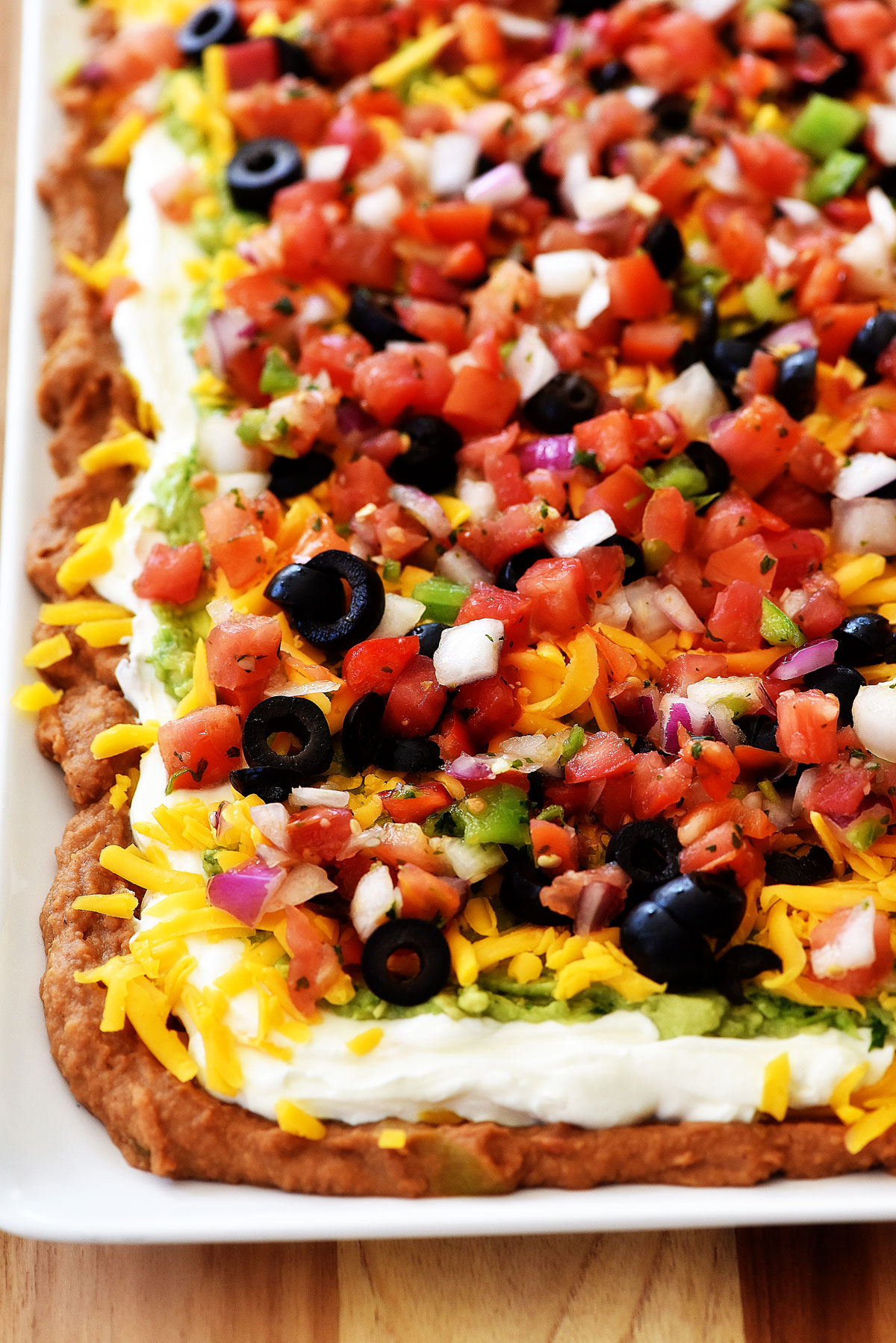Mexican layer dip is a delicious dip with layers of beans, sour cream, guacamole and pico de gallo. Life-in-the-Lofthouse.com