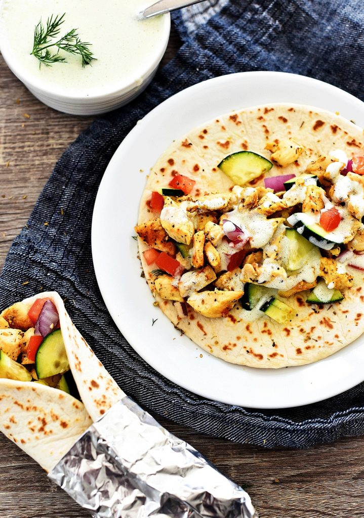 Greek Chicken Wraps are loaded with veggies, seasoned grilled chicken and Tzatziki sauce all wrapped inside a warm flatbread. Life-in-the-Lofthouse.com