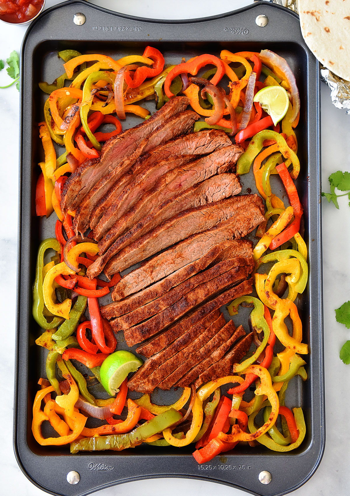 Sheet Pan Steak Fajitas are just like classic fajitas with grilled onions, bell peppers and steak. Life-in-the-Lofthouse.com