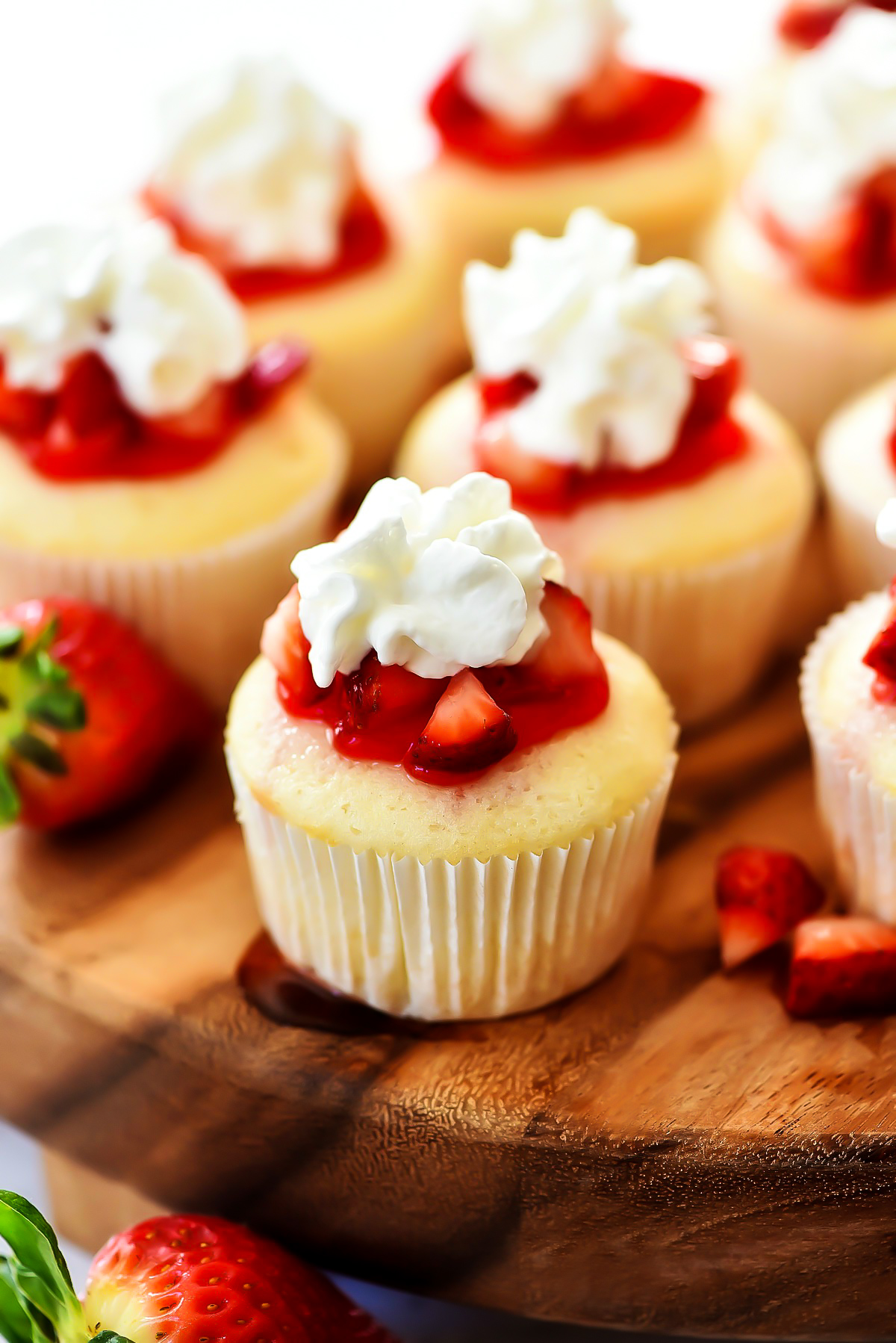 Strawberry Shortcake Cupcakes are white cakes that are light as air and topped with strawberries, glaze and whipped cream. Life-in-the-Lofthouse.com