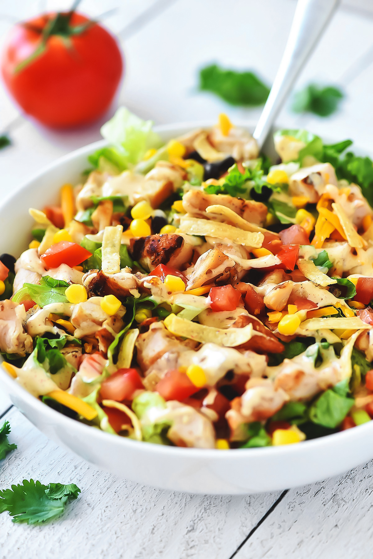 This Tex-Mex Chicken Chopped Salad is filled with crunchy romaine lettuce, corn, black beans, grilled chicken and more. The taco-flavored ranch dressing finishes it off to perfection!