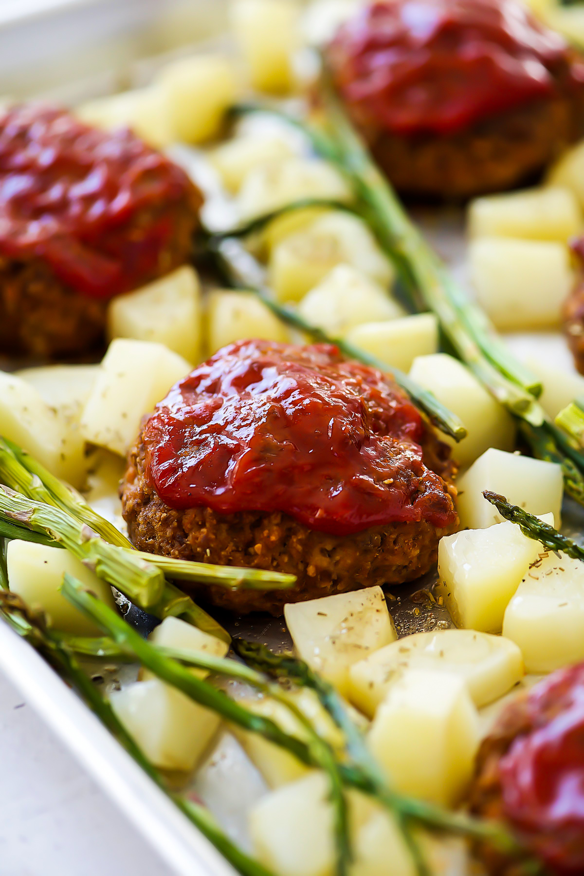 Sheet Pan Meatloaf dinner is individual mini meatloaves, asparagus, and potatoes all cooked to perfection on one pan