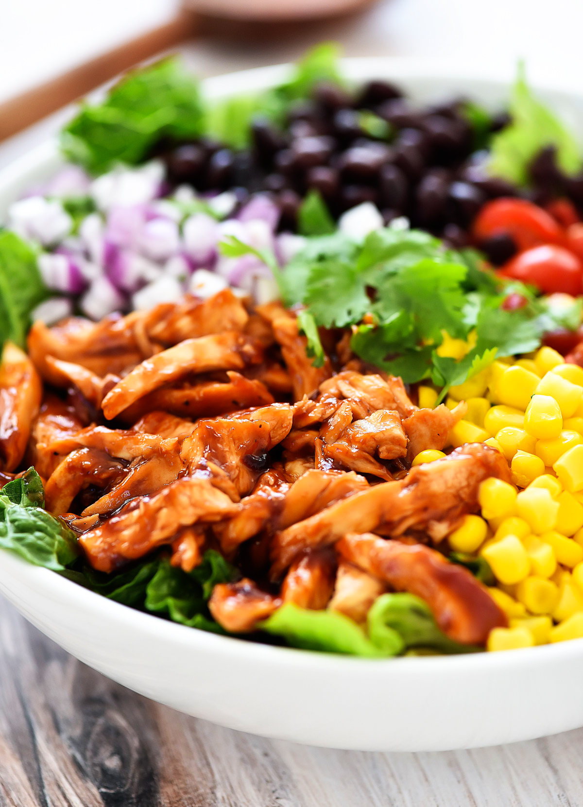 BBQ Chicken Salad is filled with romaine lettuce, bbq chicken, black, beans, corn, tomatoes and more!