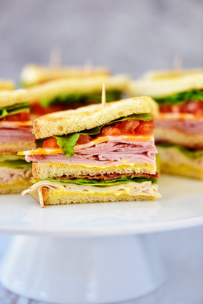 Club Sandwiches are stacked with ham, turkey, cheese, lettuce and tomato with a mustard and mayo mixture.