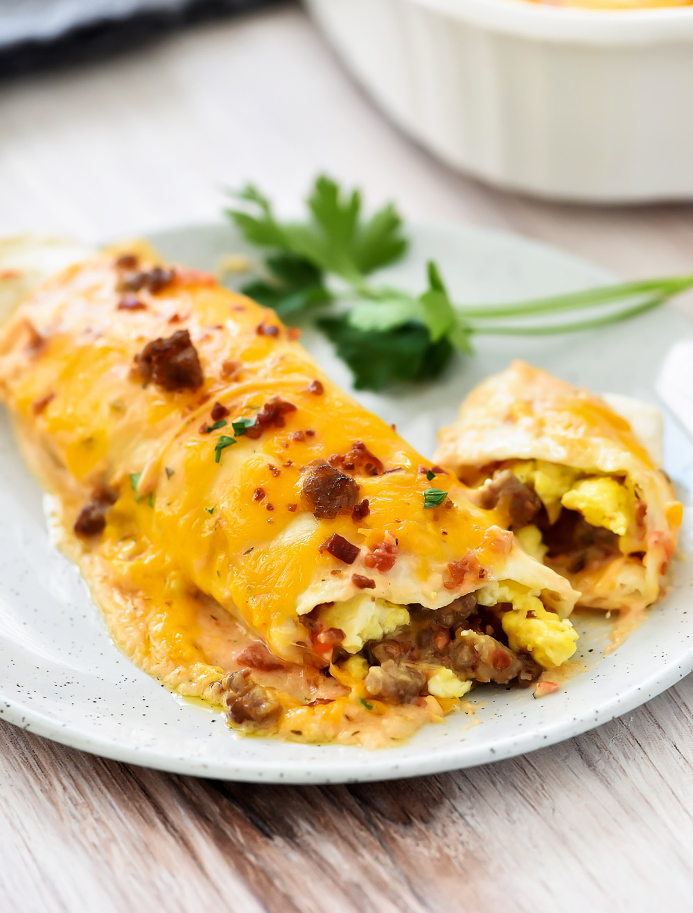 Breakfast Enchiladas are filled with eggs, bacon, sausage and cheese covered in flour tortillas and enchilada salsa. Life-in-the-Lofthouse.com