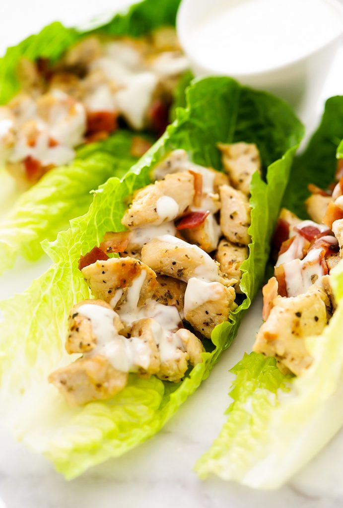 Seasoned chicken and crumbled bacon are filled inside of romaine lettuce leaves. They are topped off with ranch dressing.