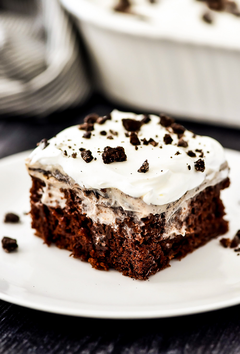Oreo Pudding Poke Cake starts with a chocolate cake, then holes are poked in the cake and Oreo Pudding is poured inside the holes. The cake is topped off with cool whip and crushed Oreo cookies.