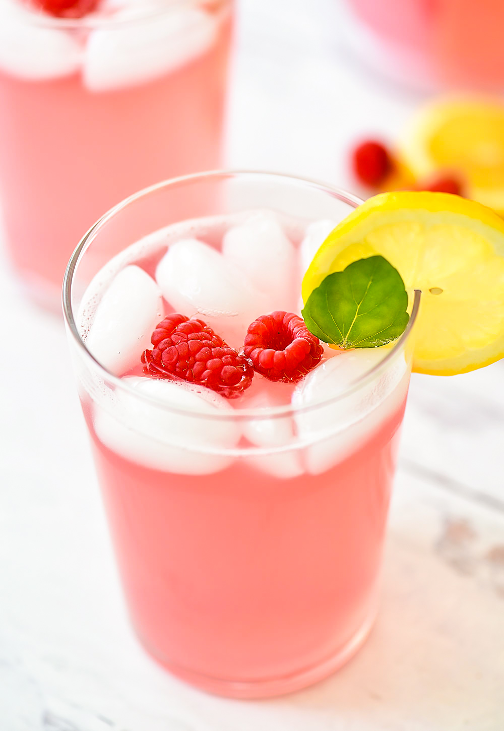 Lemonade with raspberry flavor. Garnished with raspberries, lemon and mint leaves.