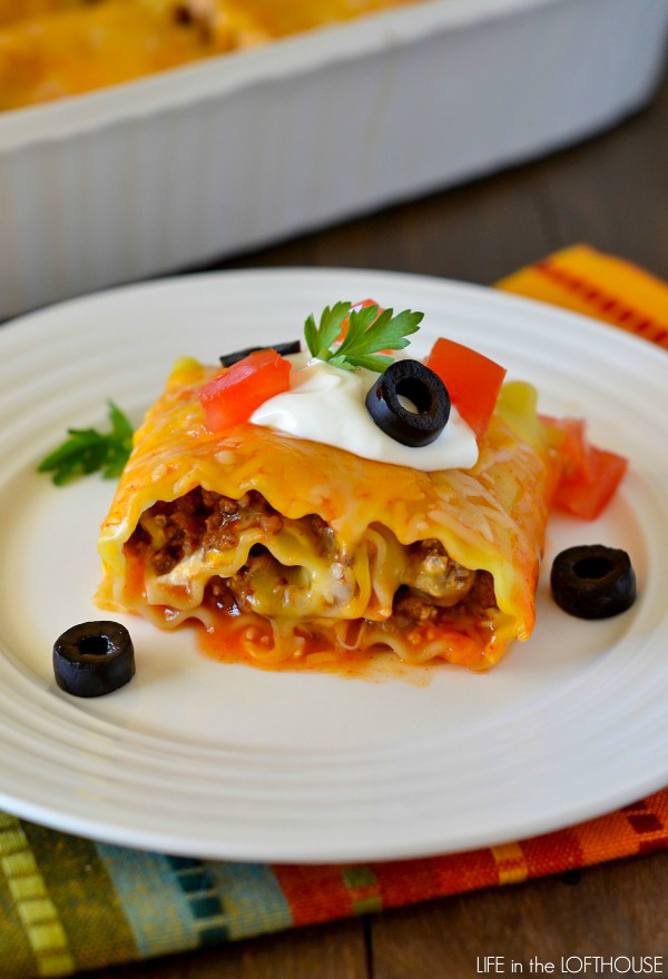 Beef enchilada lasagna roll ups are made up of Beef, enchilada sauce and taco seasoning wrapped up in lasagna noodles and covered in gooey cheese. Life-in-the-Lofthouse.com