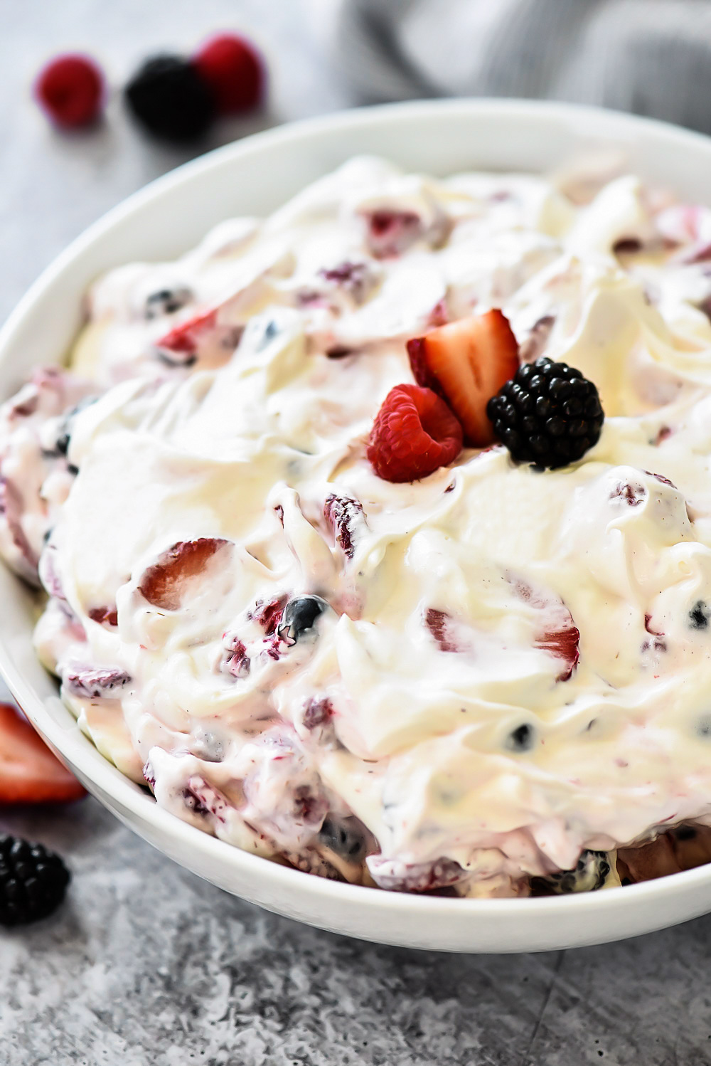Sliced strawberries, blueberries, blackberries and raspberries covered in a sweet cream cheese fluff. Life-in-the-Lofthouse.com