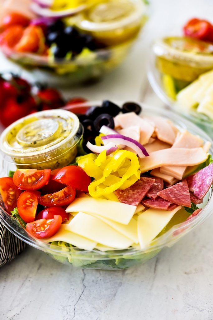 Italian Sub Salad is filled with sliced turkey, salami, provolone cheese, banana peppers, sliced olives and cherry tomatoes. Life-in-the-Lofthouse.com
